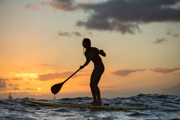 Young woman on Standup Paddle Board, SUP, off shore at Waikiki Beach, on Oahu, Hawaii?s southern shoreline.